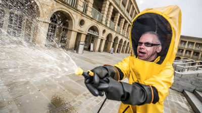 Howard Davies wearing a bright yellow hazmat suit with black latex gloves, pointing and firing a hose