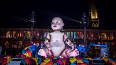A giant sculpture of a baby with bright blue eyes and with puppetry arms being moved by several puppeteers