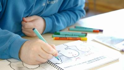 A child holding a felt tip pen with an open book